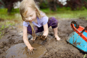 outdoor photograph of girl playing in mud